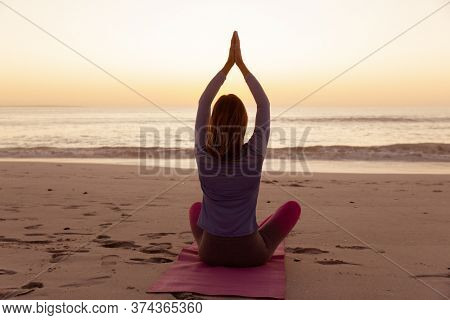 Attractive blonde Caucasian woman enjoying time at the beach at sundown, practicing yoga with hands in a prayer position, with sunset sky and sea in the background. Summer tropical beach vacation.
