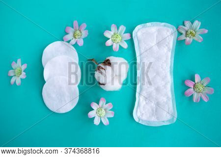 Sanitary Pad And Cotton Sponges On Green Background, Top View