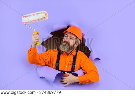 Painter. Painter With Painting Roller Through Hole In Paper. Bearded Worker With Paint Roller. Profe