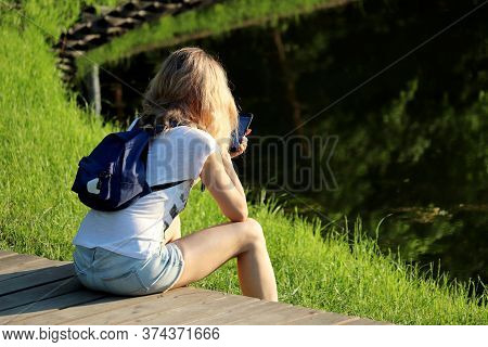 Slim Girl In Short Jeans Shorts With Backpack Sitting With Smartphone On A Beach In A Summer Park. C