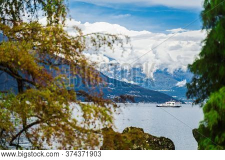 Ferry On Lake Como, Northern Italy. The Boat Is Moving On The Lake Against The Background Of The Alp