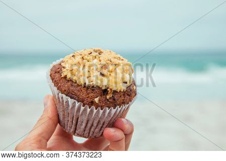 Woman's Hand Holding A Muffin (cupcake) Cake With Cream And Nuts On A Background Of Nature. Concept