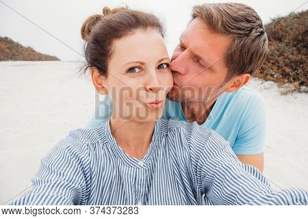 Image Of Young Happy Man Kissing And Hugging Beautiful Woman While Taking Selfie Photo On Sunny Beac