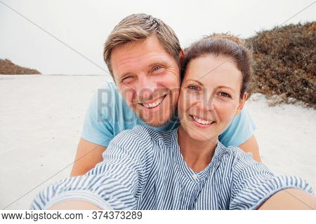 Travel, Tourism, Summer Vacation, Technology And Love Concept - Happy Couple Taking Selfie With Smar