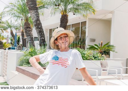 Pretty Happy Woman In Hat And T-shirt With American Flag Posing In Front Of Her House On A Sunny Day