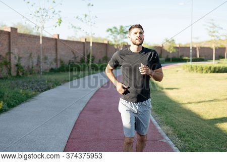 Handsome Hispanic Young Man Jogging On Footpath In Park
