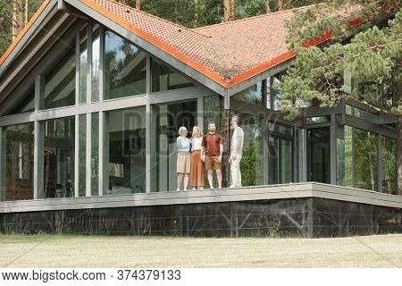 Young daughter and son standing with senior parents against beautiful cottage and contemplating nature around