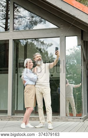 Handsome senior bearded man hugging wife while taking selfie with him near glass house