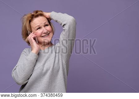 Old Caucasian Lady Talking On Mobile Phone, Smiling, Looking Away