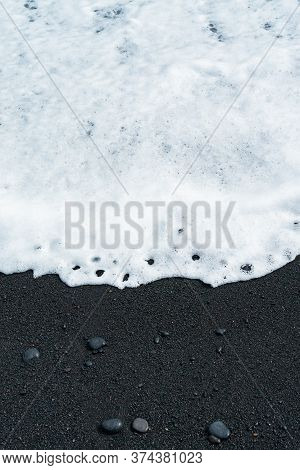 Oceanic Wave With White Foam Rolls Over Black Sand Beach With Pebble . Silky Black Beach Texture. Mi