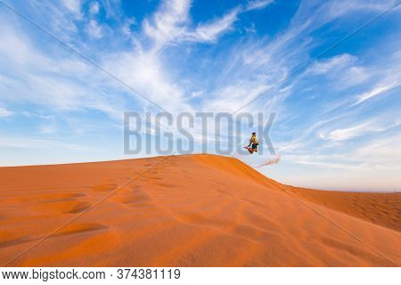 Young Man On Red Sand Dunes In Vietnam