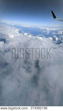 Aerial High In The Sky, Shot From Above The Clouds, With The Wing Of A Commercial Jet Plane That Tur