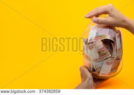 Hands Holding A Three-liter Jar In Which Lie Five Thousandth Bills
