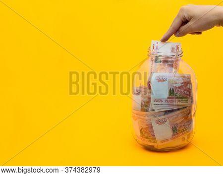 Finger Stuffs Another Five Thousandth Bill Into A Glass Jar