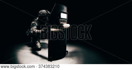 Portrait Of A Special Forces Unit Fighter. He Hides Behind A Bulletproof Shield. Black Background. T