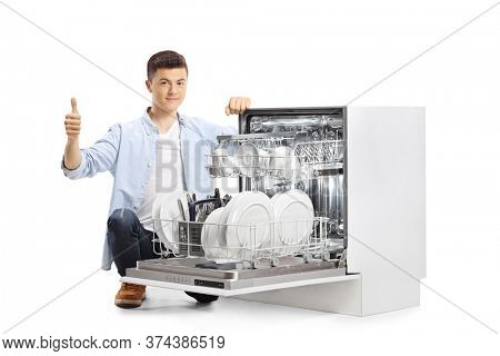 Teenager kneeling next to a dishwasher and showing thumbs up isolated on white background