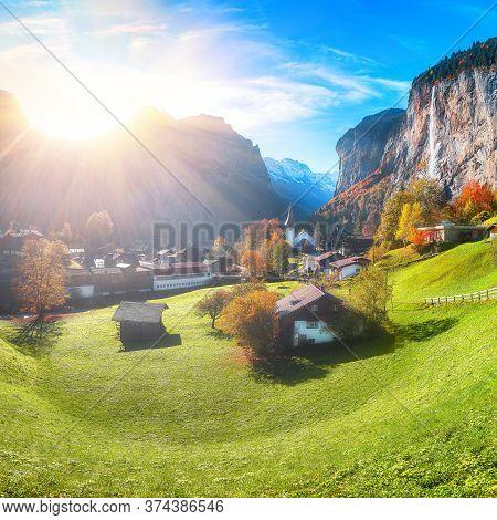 Stunning Autumn Landscape Of  Alpine Village Lauterbrunnen With Famous Church And Staubbach Waterfal