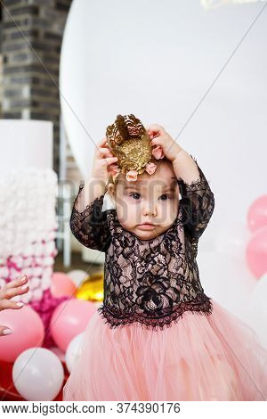 Photo Portrait Of A Birthday Girl 1 Year Old In A Pink Dress With Pink Balloons. The Child Cries At