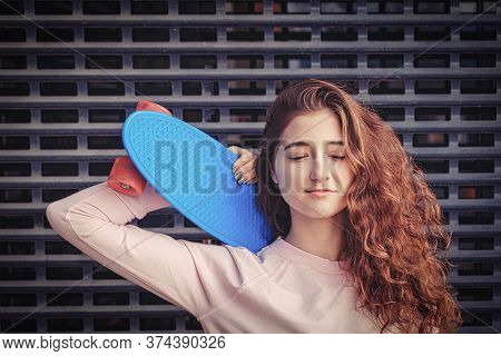 Ginger Haired Lady Daydreaming With Her Eyes Closed. She Is Holding Her Pennyboard On Her Shoulder