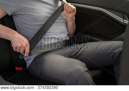 Male Passenger Fastens His Seat Belt In A Car. Passive Safety System In Transport.