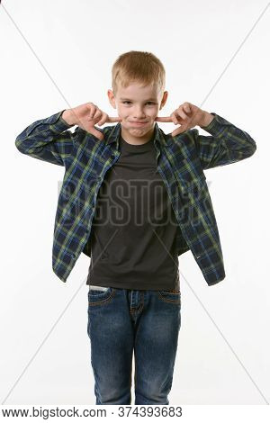 Boy On A White Background In A Plaid Shirt Blows His Cheeks With His Fingers