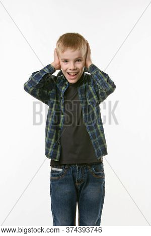 The Boy Covers His Ears With His Hands And Shouts Looking Into The Frame Against A White Background