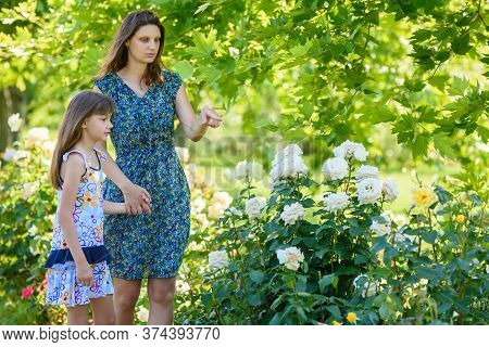 Mom And Daughter Walk In The Garden With Roses