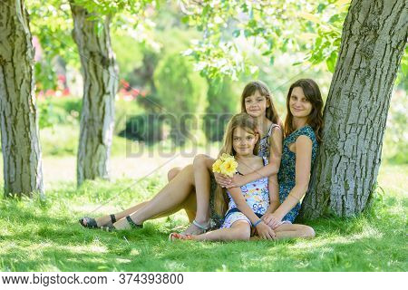 Mom With Two Daughters Sits On Green Grass Near Tree In Park