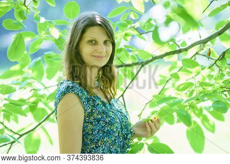 Girl Smiles Against A Branch With Green Leaves In Sunny Weather
