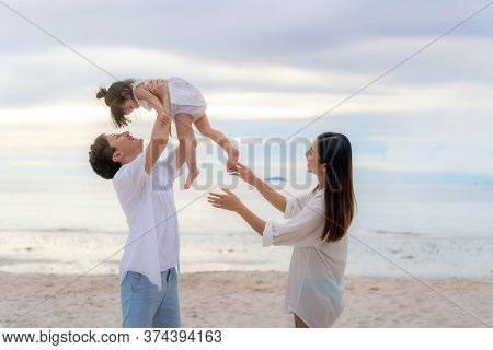 Happy Asian Family Holidays During Joyful Father, Mother And Daughter Walking And Raise Daughter To