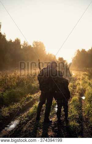 Father And Son Hunting Together. Walking The Road After The Bird Hunt.