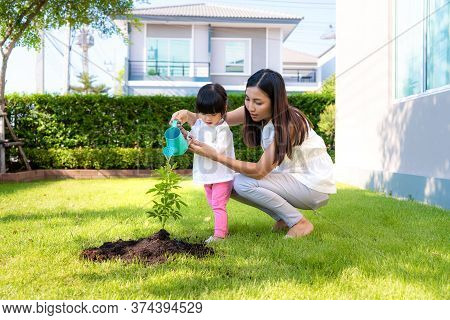 Asian Family Mother And Kid Daughter Plant Sapling Tree And Watering Outdoors In Nature Spring For R