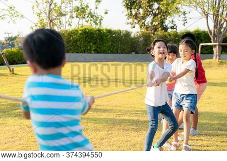 Group Of Happy Young Asian Children Playing Tug Of War Or Pull Rope Togerther Outside In City Park P