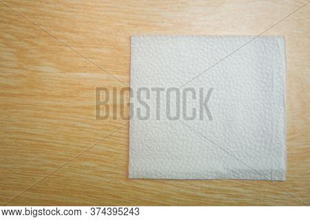 Blank Paper Napkin Isolated On Wooden Background With Copy Space . White Napkin On Wooden Background