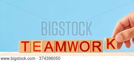 Teamwork Concept. Man Stacks Wooden Blocks In The Inscription Teamwork