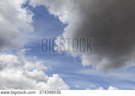 Beautiful White Clouds And Blue Sky With Some Grey Rain Clouds. Nature Background With No People