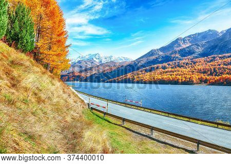 Fantastic Autumn Scene On  Sils Lake (silsersee) And Asphalt Road In The Front. Colorful Autumn Scen