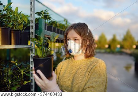 Young Woman Choosing And Buying Seedlings Of Rhododendron In Garden Center In Early Springtime. Land