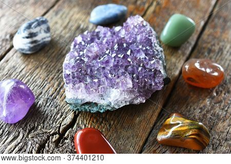 A Close Up Image Of Chakra Crystals Surrounding Am Amethyst Geode Cluster.