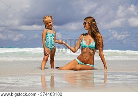 Beautiful Sexy Young Caucasian Woman In Blue Bikini And Little Girl On The Sandy Beach. Summer Famil