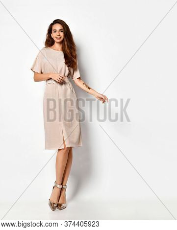 Tender Long-haired Young Woman Posing In Knee-length Light Powder-pink Dress With Belt And Silver Hi