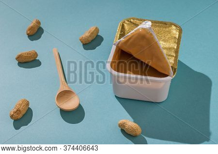 Container With Peanut Paste, Peanuts And A Spoon On A Blue Background In Bright Light. Natural Peanu