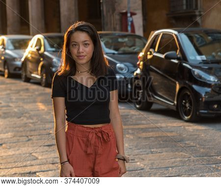 Young Asian Teen In Black Blouse Standing On Stone Street In Front Of Building In Black Blouse In Bo