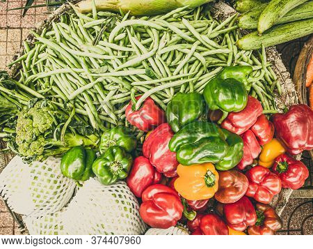 Close-up Heap Of Pile Raw Red Green Yellow Bell-pepper, Green Beans And Broccoli On A Local Asia Far