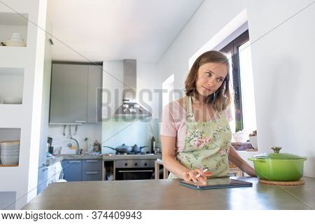 Pensive Young Woman Consulting Internet While Cooking In Her Kitchen, Using Tablet Near Big Saucepan