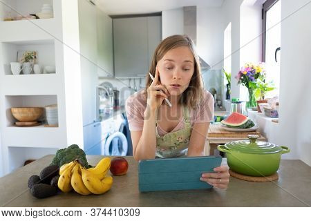 Excited Woman Watching Online Cooking Class In Her Kitchen, Leaning On Table, Using Tablet Near Sauc