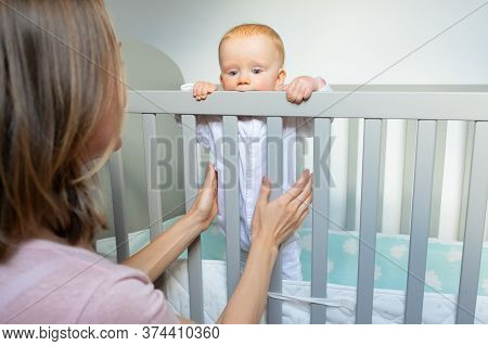 Mother Training Baby To Stand In Crib, Holding And Supporting Child. Toddler Standing In Crib And Ho