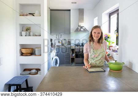 Joyful Housewife Writing Notes On Pad For Recipe While Cooking In Her Kitchen, Using Tablet Near Big