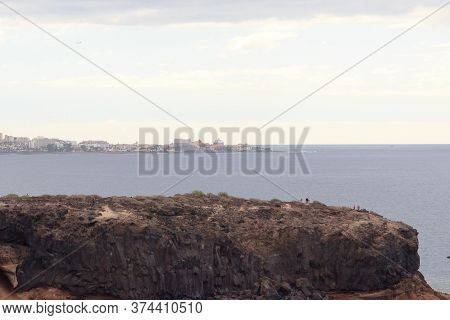 Cliff With Town Playa De Las Americas In The Background On Canary Island Tenerife, Spain