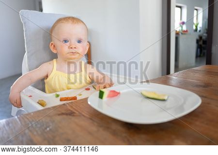 Adorable Baby Girl Sitting In Highchair With Food Messy On Tray And Face, Trying To Eat Pieces Of Fr